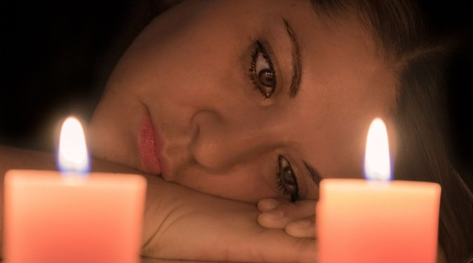 Depressed woman by lit candles