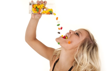 woman pouring jelly beans mouth