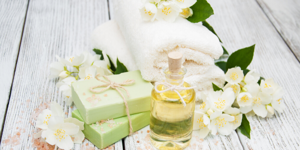 white flowers with bottle of essential oil and bar soap