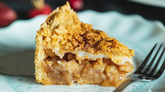 slice of warm apple pie on plate with fork