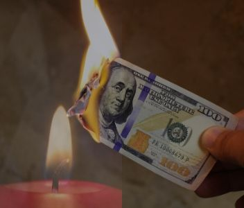 Red burning candle catching money on fire