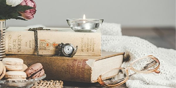 Burning candle on top of books with reading glasses and stopwatch