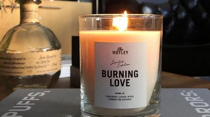 The Motley Burning Love white soy candle burning on desk