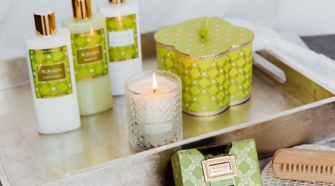 Agraria San Francisco candle burning on silver tray with green gift box and bath body products