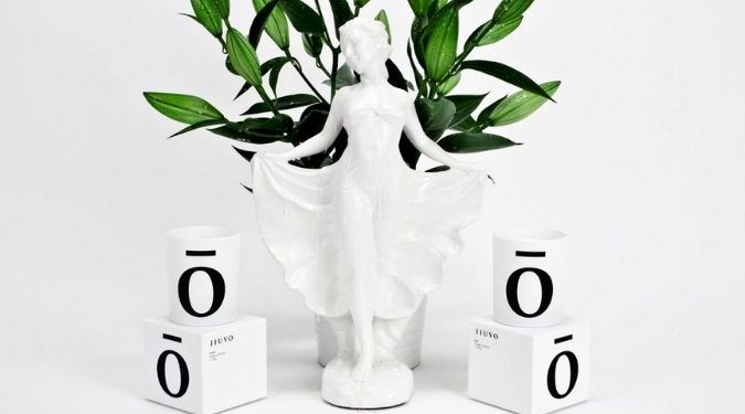 Iiuvo white candles by white figurine and green plant